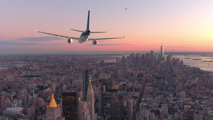AERIAL: Passenger airplane flying over downtown Manhattan at beautiful sunset.