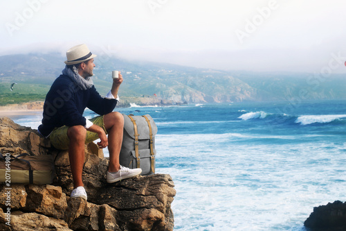 Foto Murales Traveler drinking coffee against the waves of the ocean
