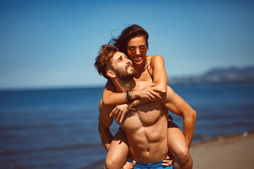 Young happy couple in a embrace on the beach © djile