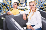 smiling businesswomen with paper cups of coffee at modern coworking office - 207179147