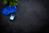 Healthy sleep concept. Sleeping mask near alarm clock on black background top view copy space - 207180930