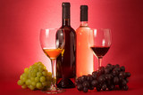 Red and white wine bottles; grape an drinking glasses - 207202590