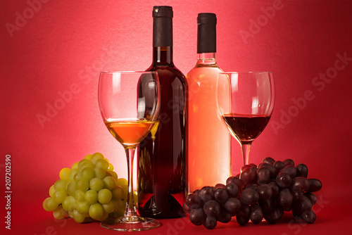 Foto Murales Red and white wine bottles; grape an drinking glasses