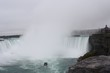 Mist rising from Niagara Falls with boat
