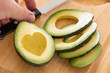 Male Hand Prepares Fresh Cut Avocado With Heart Shaped Pit Area On Wooden Cutting Board