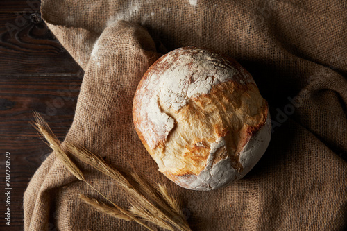 top view of bread, wheat, sackcloth covering by flour on wooden table