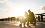 Happy couple - young woman with disabled man in wheelchair rests together outdoors - 207230935