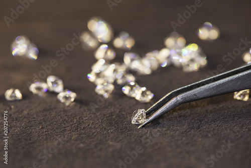 Diamond with tweezers and magnifier.Gemstone Beauty © tonjung