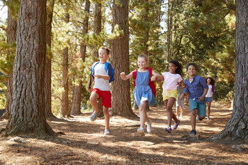 Children Running Ahead Of Parents On Family Hiking Adventure