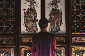 Tourist stands in front of mysterious, beautiful, Chinese gate