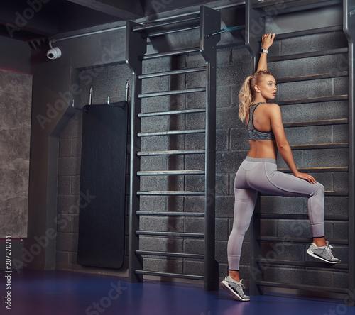 Beautifull fitness kobieta robi rozciąganie oparty na ścianie barów w nowoczesnym centrum fitness.