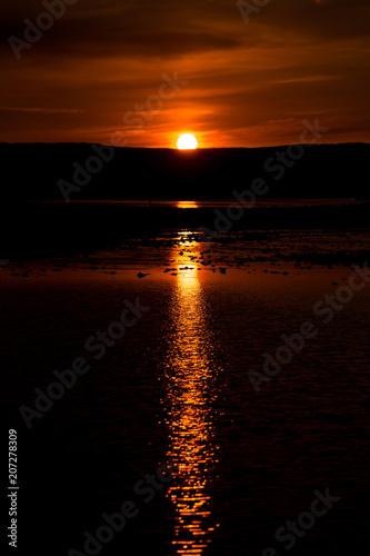 Fotobehang Bruin Sunrise reflection in water on a hot summer day in Skye Island, Scotland