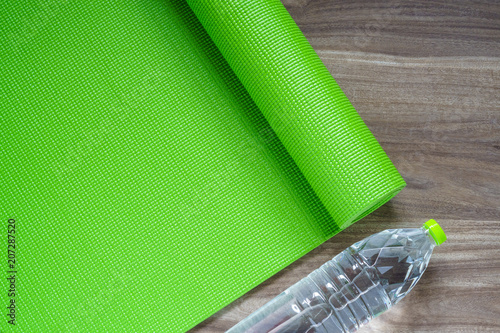 Leinwanddruck Bild Green yoga mat on a wooden background with water bottle, Top View with copy space. Active healthy lifestyle background concept.
