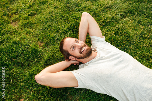 Leinwanddruck Bild Photo from top of smiling handsome man wearing white t-shirt, spending leisure time in green park lying on grass and putting hands behind his back