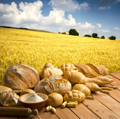 bread on the wooden table in a field of wheat