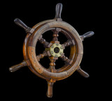 Ship steering wheel on black background.