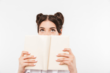 Photo of dreaming teenage girl with double buns hairstyle reading and looking upward while covering face with book, isolated over white background © Drobot Dean