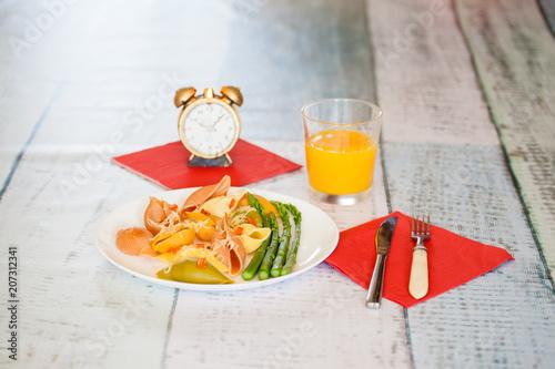 Aluminium Sap Macaroni with asparagus on a white plate, orange juice and household items