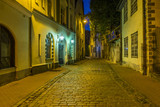 Medieval street by night in old Riga, Latvia, Europe. In old Riga tourists can find unique medieval architectural ensembles and ancient buildings - 207313116