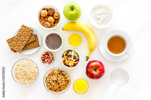 Foto Murales Ingredients for healthy breakfast. Fruits, oatmeal, yogurt, nuts, crispbreads, chia on white background top view