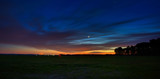 Venus in the night sky with stars. A bright sunset with clouds. Cosmic space above the earth's surface. Long exposure.
