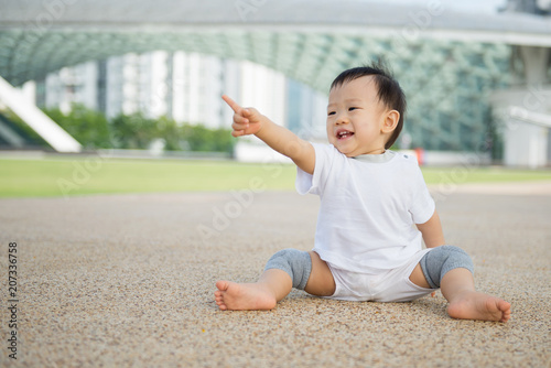 Foto Murales Beautiful baby boy crawling outdoor in park, learn to walk