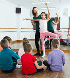 satisfied boys and girls rehearsing ballet dance in studio