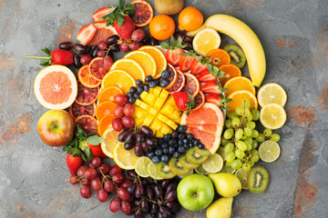 Healthy fruits background in rainbow colours oranges apples grapes pears mango strawberries kiwis on the grey concrete table, top view, copy space, selective focus © Liliya Trott
