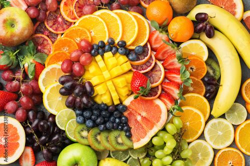 Foto Murales Healthy fruits background oranges apples grapes pears mango strawberries kiwis satsumas, top view, copy space, selective focus