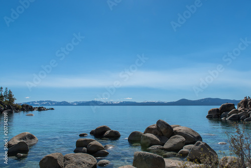Aluminium Blauwe jeans Rocks in Lake Tahoe with snow capped mountains in background.