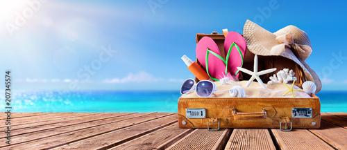 Beach Accessories In Suitcase On Wooden Pier - Travel Concept  © Romolo Tavani