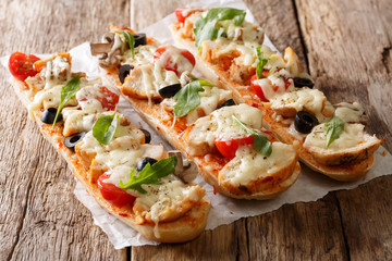 Hot tasty cut baguette baked with chicken, cheese, tomatoes, olives and mushrooms close-up. horizontal