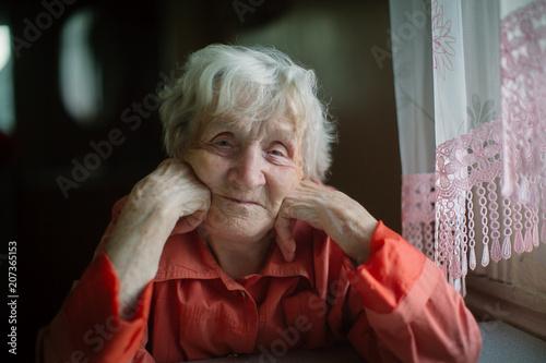 An elderly woman sits near the window in house.