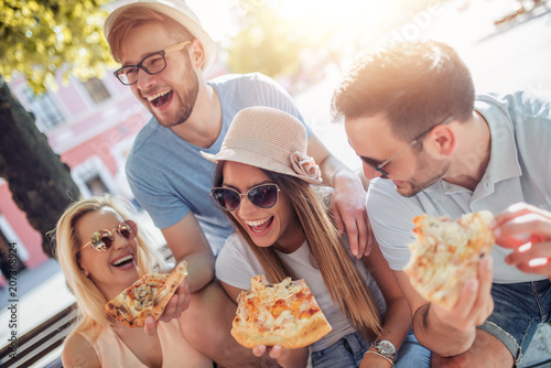 Friends having fun and eating pizza in the city