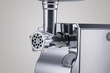household electric meat grinder with nozzle on light grey background, close-up. kitchen appliances