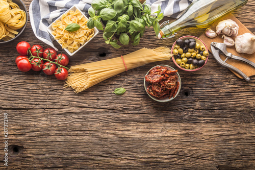 Italian food ingredients pasta olive oil parmesan cheese basil garlic mushrooms tomatoes olives on wooden table - 207372149
