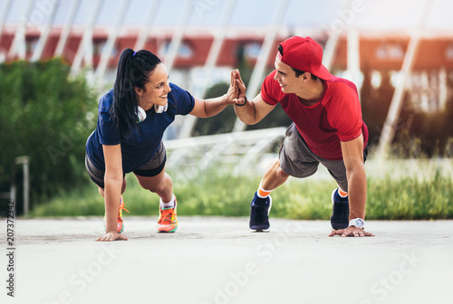 Plexiglas Fitness fitness, sport, people and lifestyle concept - man and woman exercising outdoors