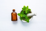 Essential Oil in a Glass Bottle with mint leaves