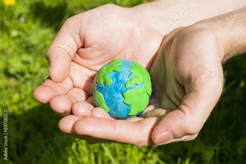 Foto Murales Plasticine Earth in man`s hand on the natural background.