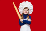Happy little girl in chef uniform holds rolling pin isolated on red. Kid chef. Cooking Process Concept  - 207388564
