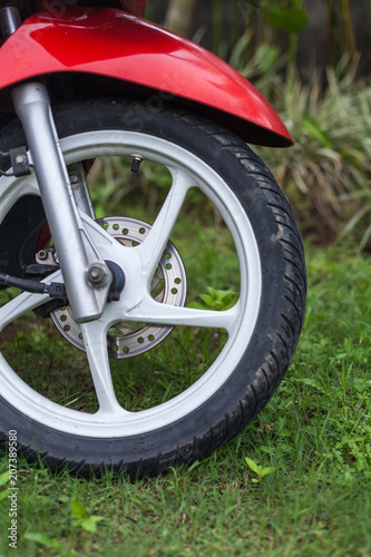 Plexiglas Scooter Fragment of front wheel with disc brakes of a red scooter