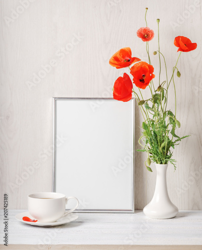 Red poppies bouquet in vase, tee cup and frame for text.