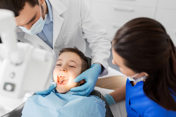 medicine, dentistry and healthcare concept - dentist with mouth mirror checking for kid patient teeth at dental clinic