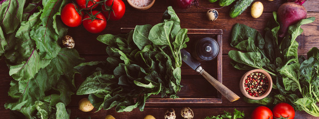 spinach in a box, fresh vegetables, wooden background, banner