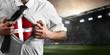 Denmark soccer or football supporter showing flag under his business shirt on stadium.