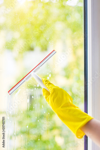 glass window pane four hand cleaning glass window pane with detergent and rubber aluminum wiper female hands in