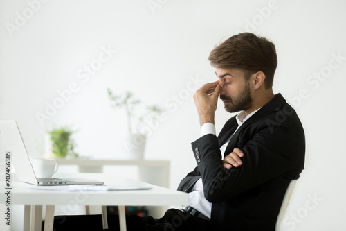 Leinwanddruck Bild Exhausted businessman feeling tired after long hours working at laptop, massaging nose bridge, suffering from eye strain, trying to relieve pain. Concept of overwork, fatigue at workplace