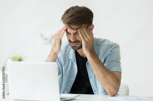 Leinwanddruck Bild Exhausted male worker massaging head, suffering from severe headache, tired after long working hours in office, trying to relieve pain and relax. Concept of overwork, physical discomfort, sickness