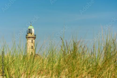 Fotobehang Vuurtoren Leuchtturm in Warnemünde mit Gräsern des Ostseestrandes im Vordergrund