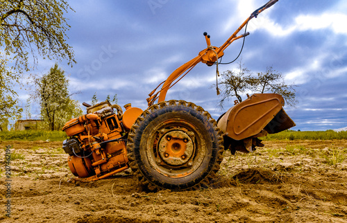 Fotobehang Trekker A small hand-held tractor, a motoblock, plows the earth. Against the background of the blue sky. Concept agriculture and industry
